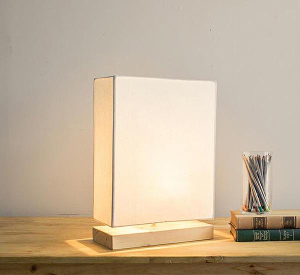Chiếc đèn mang dáng hình hộp chữ nhật dẹt với đế đèn gỗ đơn giản